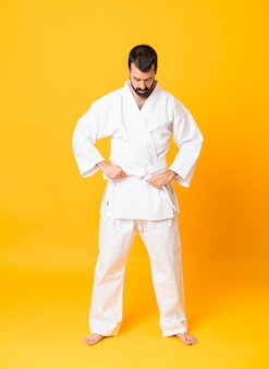 Schuss in voller länge des mannes über dem lokalisierten gelben hintergrund, der karate tut