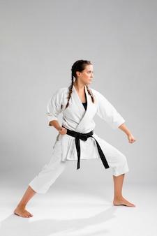 Schuss in voller länge einer frau mit übendem karate des schwarzen gürtels und des kimonos