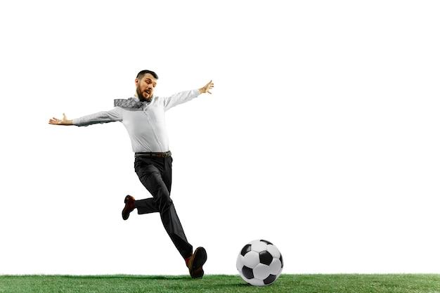 Schuss in voller länge eines jungen geschäftsmannes, der fußball spielt, lokalisiert auf weißer wand