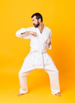 Schuss in voller länge von mandoing karate über lokalisiertem gelbem hintergrund