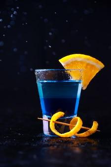 Schuss mit weißem rum, liquor blue curacao und orange slice. alkoholische schicht cocktail in freeze motion, tropfen in liquid splash auf dunkle wand