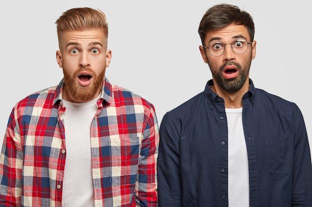 Schuss von attraktiven männlichen begleitern starren mit verängstigten schockierten ausdrücken, kann nicht an eine nicht bestandene prüfung glauben, angst, von der universität ausgeschlossen zu werden, mit angehaltenem atem vor erstaunen schauen