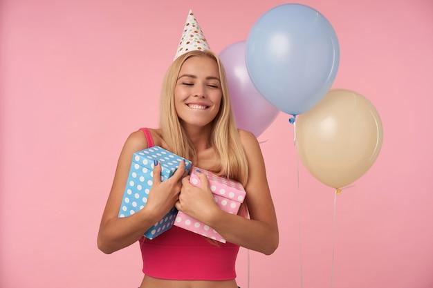Schuss von entzückter ziemlich langhaariger frau mit lässiger frisur, die geburtstag mit mehrfarbigen luftballons feiert und glückliche reaktion auf fantastische geschenke zeigt, isoliert über rosa hintergrund