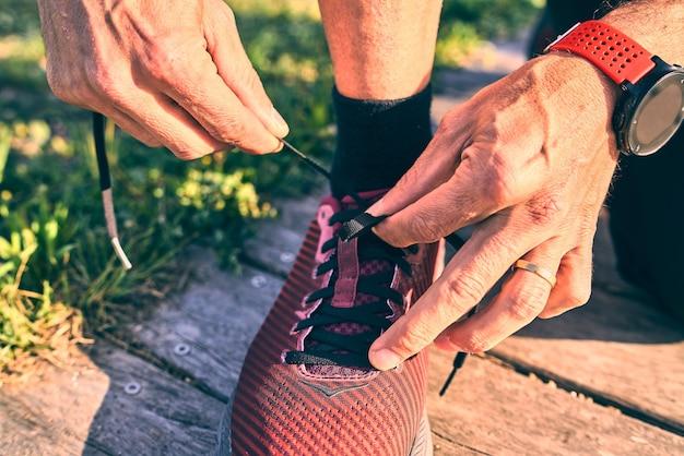 Schuss von fit mann binden schnürsenkel auf holzweg hautnah. sonniger heller tag.