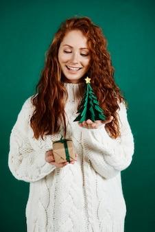 Schuss von fröhlichem mädchen, das weihnachtsgeschenk gibt