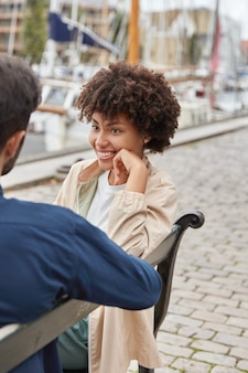 Schuss von fröhlicher attraktiver frau hat zahniges lächeln sitzt auf bank