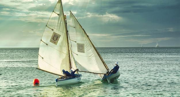 Schuss von menschen auf den weißen booten, die bei bewölktem wetter im meer schwimmen