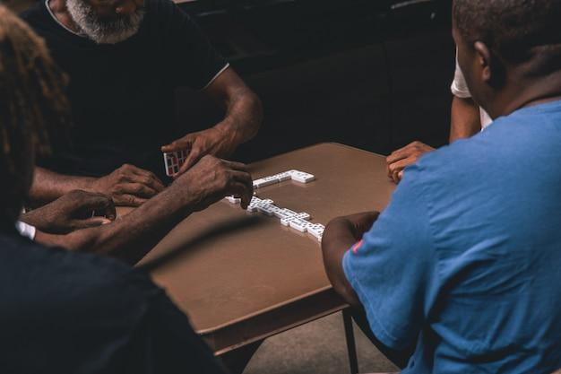 Schuss von vier afrikanischen männern, die domino auf einem tisch spielen