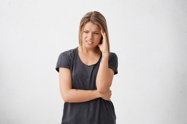 Schussansicht der besorgten erschöpften erschöpften frau mit dem traurigen und hageren stirnrunzelnden gesicht, das hand auf schläfe hält, die weint und viele probleme hat, die nicht wissen, wie man sie löst. menschen, stress und probleme