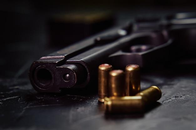 Schusswaffen auf konkretem hintergrund nahaufnahme von vorgehaltener waffe und kugeln auf tischwaffen und munitionskonz...