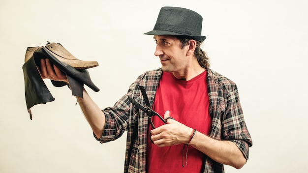 Schuster hält satz werkzeuge und leder. konzept für kleine unternehmen. handgefertigte lederschuhe. schuhmacher, der schuhe in seiner werkstatt modelliert.