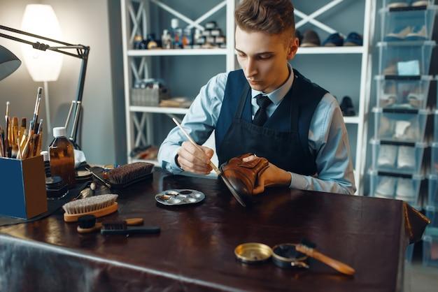Schuster wischt schwarze schuhcreme ab, schuhreparaturservice. handwerkskunst, schuhmacherwerkstatt, meisterarbeiten mit stiefeln