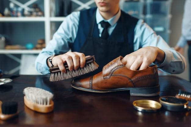 Schuster wischt schwarze schuhcreme ab, schuhreparaturservice. handwerkskunst, schuhmacherwerkstatt, meisterwerke mit stiefeln, schusterwerkstatt