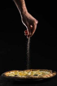 Schütten Sie Hand strömende Gewürze auf Pizza