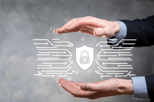 Schutz netzwerk sicherheit computer und schützen sie ihr datenkonzept, geschäftsmann hält schild schützen symbol. schlosssymbol, konzept über sicherheit, cybersicherheit und schutz vor gefahren.