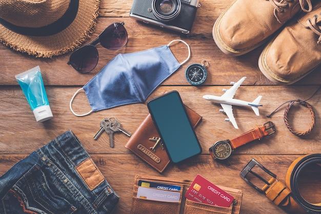 Schutz von covid-19 auf reisen. reisezubehör kostüme. reisepässe, gepäck, die kosten für reisekarten, die für die reise vorbereitet wurden .konzept neuer normaler lebensstil