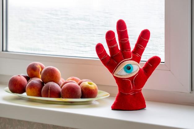 Schutzamulett in form einer offenen handfläche und eines auges aus gefilzter wolle auf einer pfirsichfensterbank