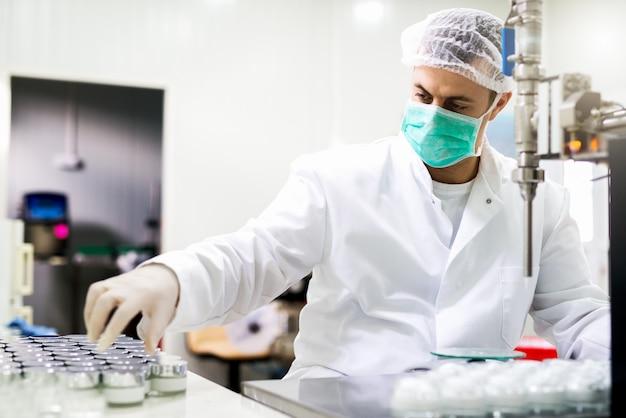 Schutzarbeiter in der pharmazeutischen fabrik an seinem arbeitsplatz.