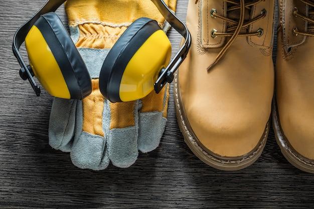 Schutzhandschuhe arbeiten spitzenstiefel ohrenschützer auf holzbrett