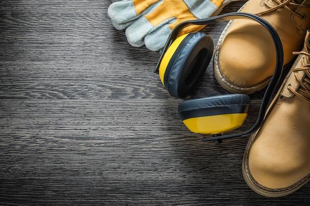Schutzhandschuhe arbeitsstiefel ohrenschützer auf holzbrett
