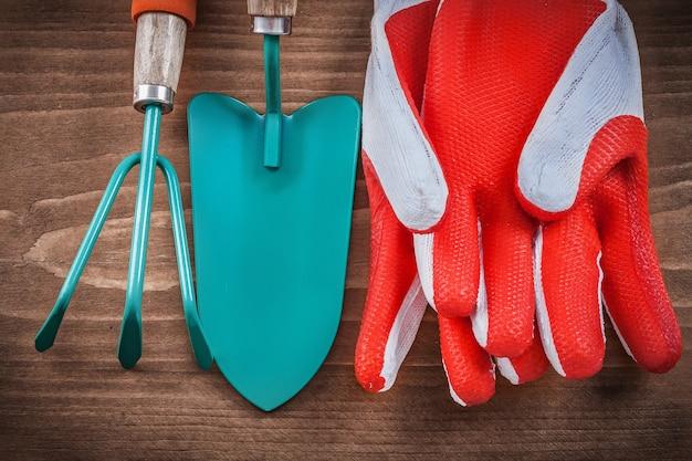 Schutzhandschuhe handspaten und rechen auf holzbrett.