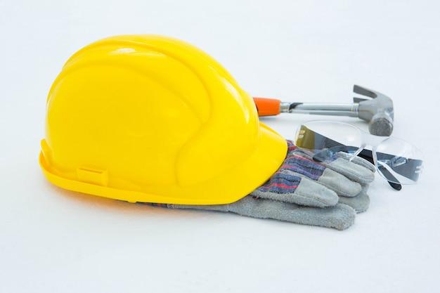 Schutzhandschuhe mit hammer, brille und gelbem schutzhelm
