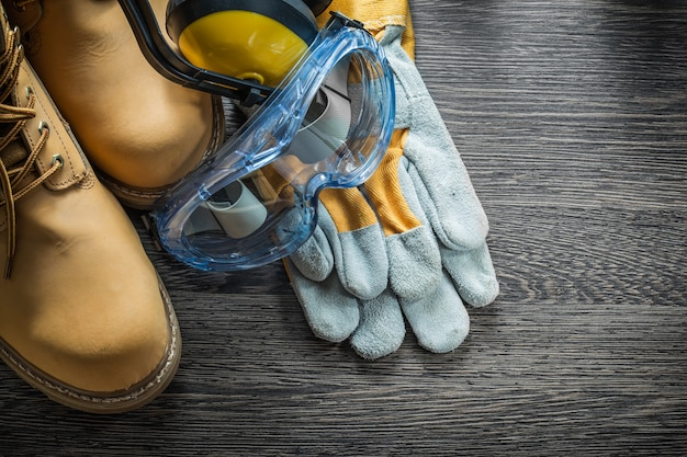 Schutzhandschuhe stiefel brille ohrenschützer auf holzbrett