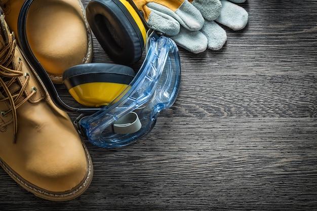 Schutzhandschuhe stiefel schutzbrille ohrenschützer auf holzbrett