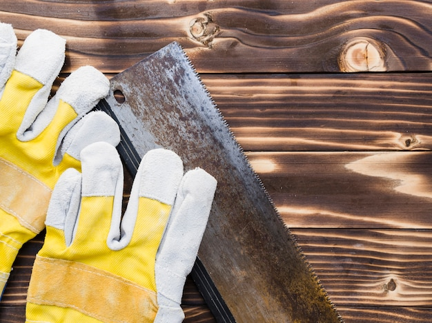 Schutzhandschuhe und säge auf dem tisch