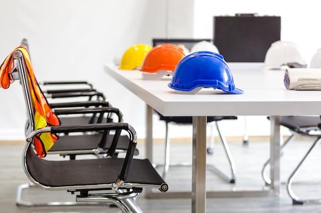 Schutzhelm auf tabelle im büro, ingenieurkonzept teamwork des hochbaus