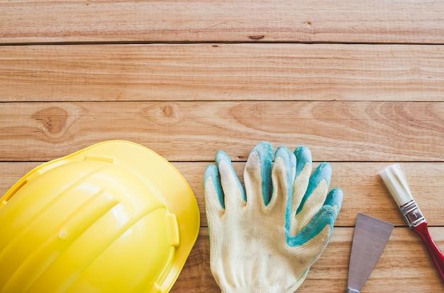 Schutzhelm, handschuhe, kelle und pinsel auf holzbrett von oben