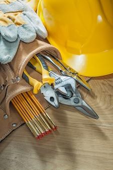 Schutzhelm sicherheitshandschuhe werkzeug gürtel werkzeug auf holzbrett