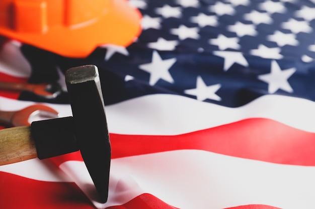 Schutzhelm und hammer auf amerikanischer flagge