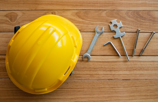 Schutzhelm und werkzeuge auf holzbrett von oben
