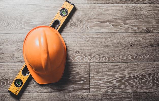 Schutzhelm und werkzeuge zum architekten auf hölzernem