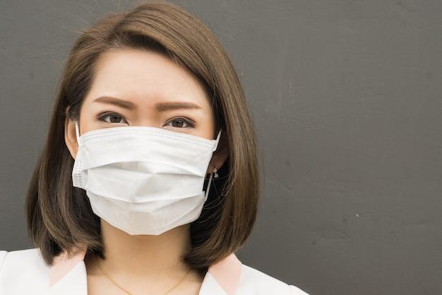Schutzmaske der asiatischen frauenabnutzung in der verschmutzungsstadt mit dem husten, kopienraum für text