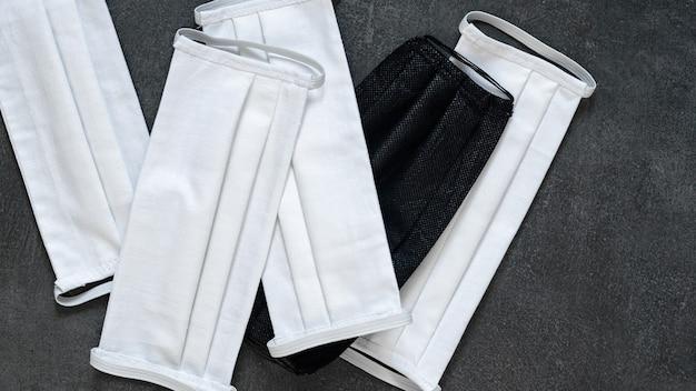 Schutzmasken handgemacht aus weißem und schwarzem stoff auf schwarzem hintergrund