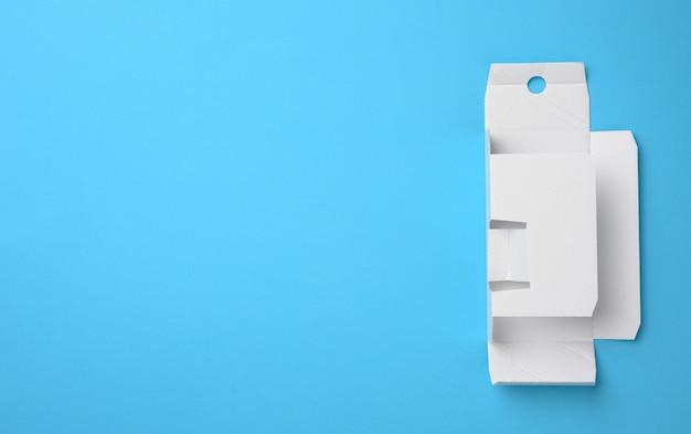 Schutzpapier unter einer schachtel mit parfüm, vorlage aus weißer wellpappe, blauer hintergrund, kopierraum