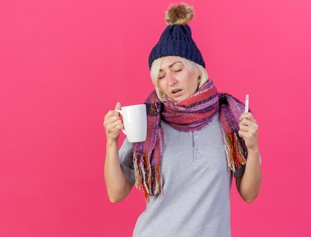 Schwache junge blonde kranke slawische frau, die wintermütze und schal trägt, hält tasse