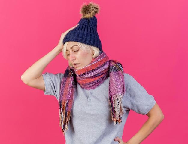 Schwache junge blonde kranke slawische frau, die wintermütze und schal trägt, legt hand auf kopf