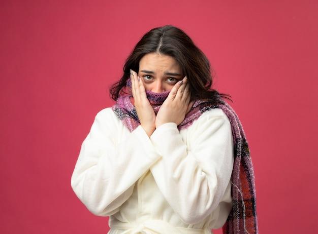 Schwache junge kranke frau, die robe und schal trägt, die mund mit schal bedeckt, der front betrachtet, die hände auf gesicht lokalisiert auf rosa wand hält