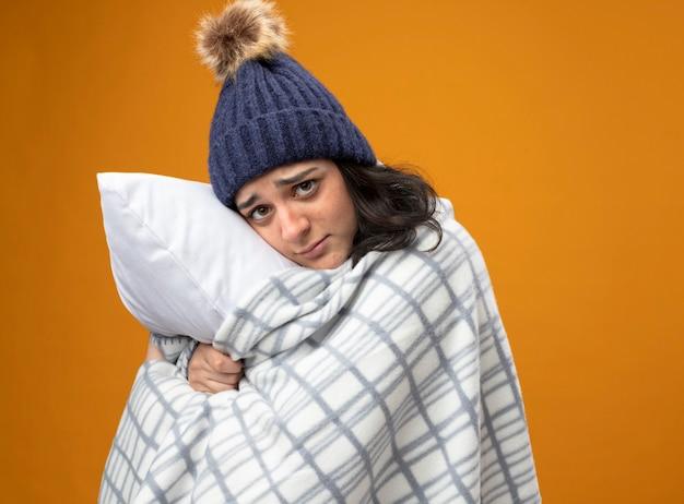 Schwache junge kranke frau, die robe wintermütze in plaid gewickelt steht in profilansicht umarmendes kissen, das front lokalisiert auf orange wand steht
