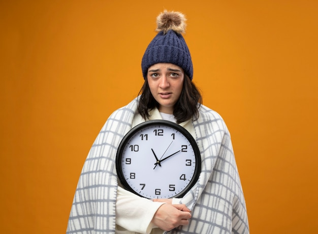 Schwache junge kranke frau, die robe wintermütze trägt, die in karierte halteuhr eingewickelt ist, die front lokal auf orange wand lokalisiert betrachtet