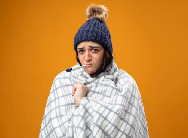 Schwache junge kranke frau, die robe wintermütze trägt, die in plaid gewickeltes plaid wickelt, das vorne mit thermometer im mund lokalisiert auf orange wand betrachtet