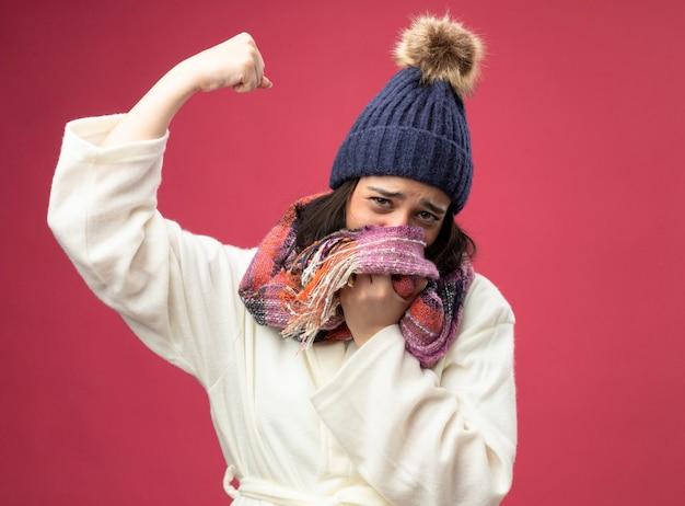 Schwache junge kranke frau, die robe wintermütze und schal trägt mund mit schal, der nach vorne schaut, macht starke geste lokalisiert auf rosa wand