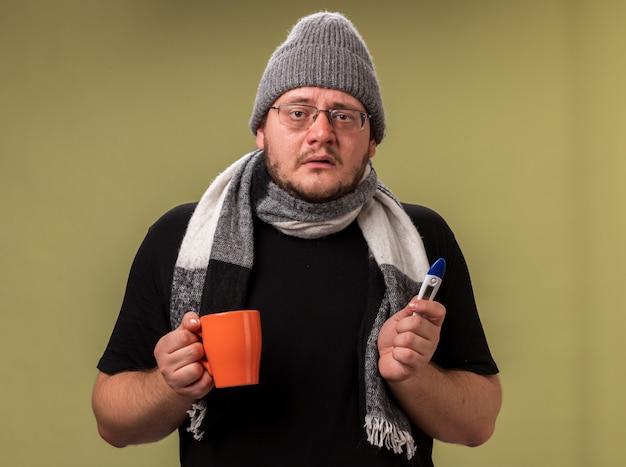 Schwacher blick in die kamera kranker mann mittleren alters mit wintermütze und schal, der eine tasse tee mit thermometer hält