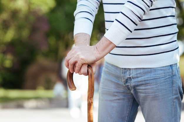 Schwacher friedlicher alter mann, der steht und sich auf den stock stützt, während er das wetter im park genießt