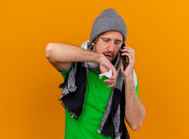 Schwacher junger gutaussehender slawischer kranker mann, der wintermütze und schal trägt, die am telefon hält, das serviette hält, die gerade hält hand in der luft lokalisiert auf orange hintergrund mit kopienraum