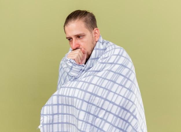 Schwacher junger gutaussehender slawischer kranker mann, eingewickelt in plaid, das seitenhusten betrachtet und faust auf mund lokalisiert auf olivgrünem hintergrund mit kopienraum hält