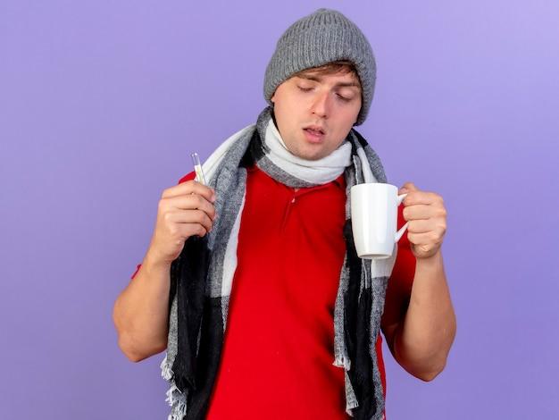 Schwacher junger hübscher blonder kranker mann, der wintermütze und schal hält thermometer und tasse lokalisiert auf lila hintergrund trägt